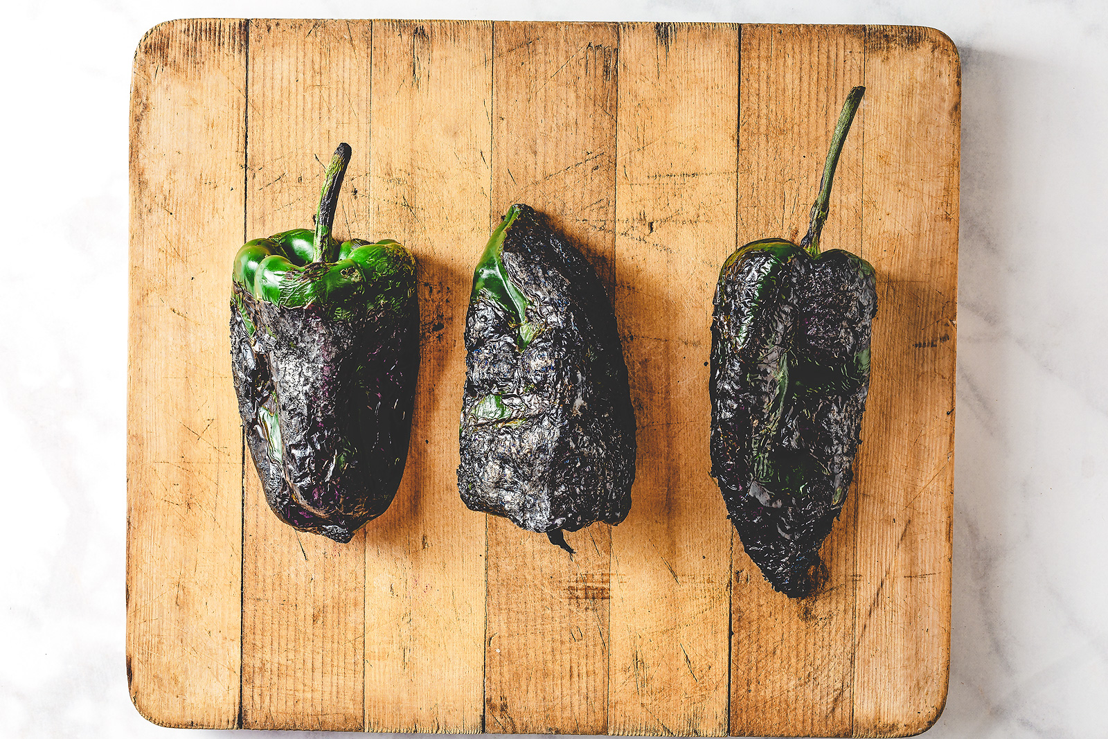 Three roasted and charred poblano peppers on a chopping board.