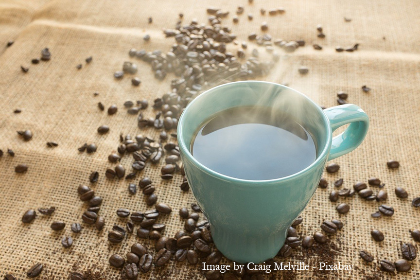 coffee cup with coffee beans on table