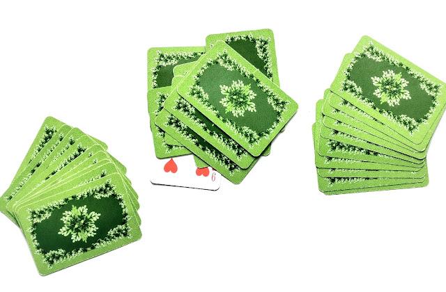 na zdjęciu stos kart odrzuconych na środku stołu a po bokach leża karty graczy ułożone w zakryte wachlarze