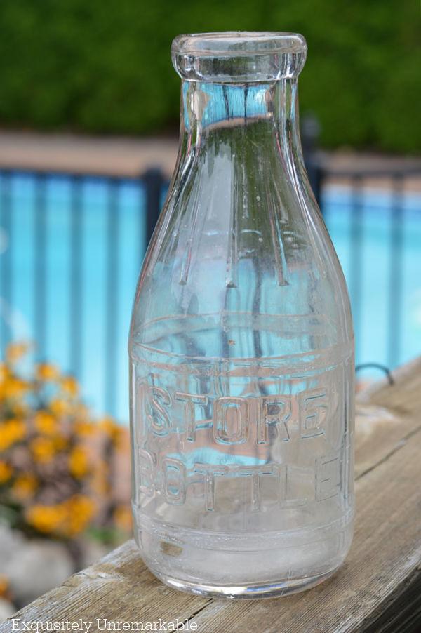 Glass Milk Bottle on a deck railing in garden