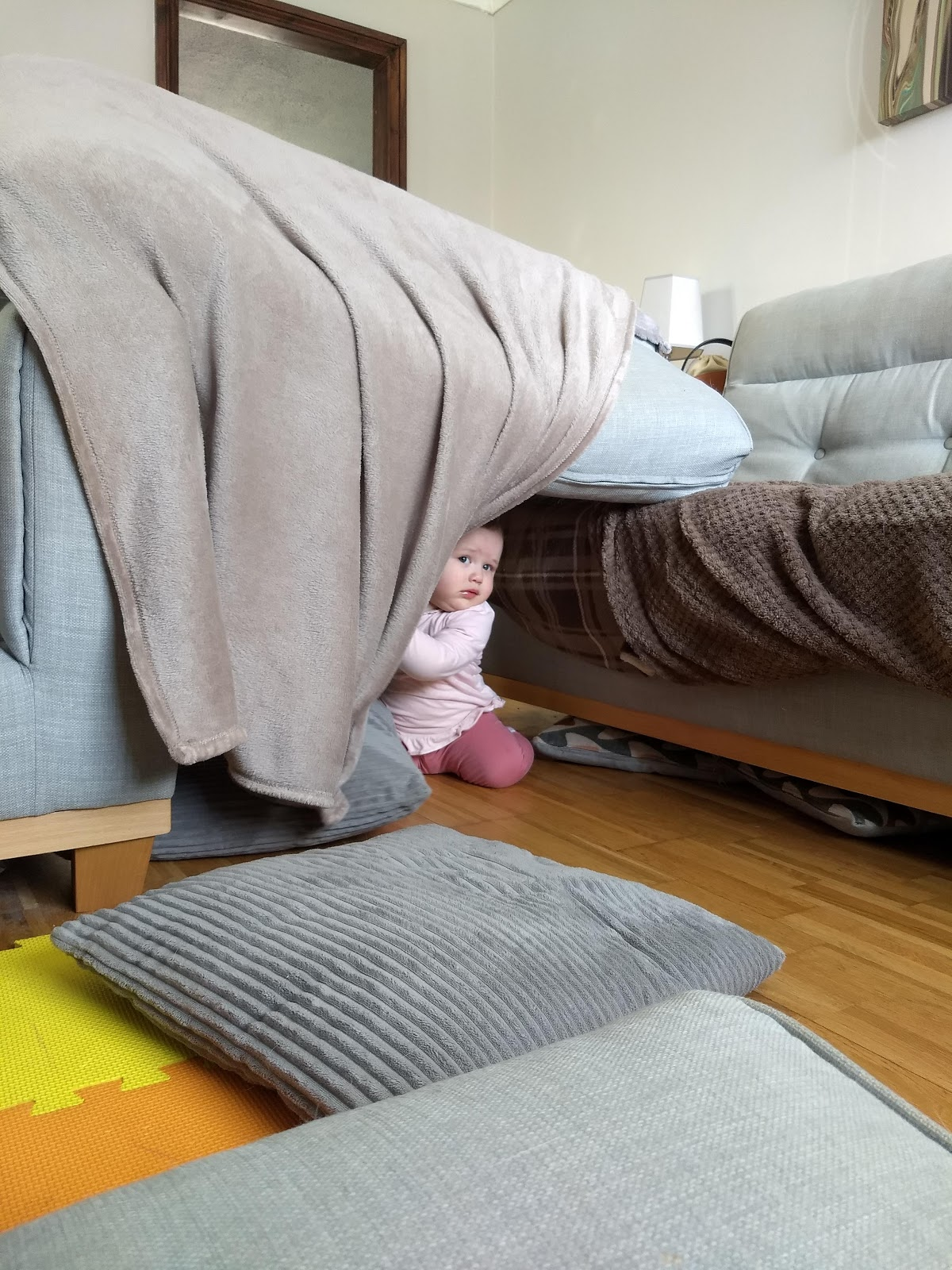 Toddler hiding under make shift den.