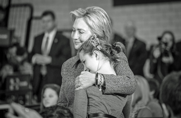 black and white image of Hillary Clinton at a rally, hugging a girl