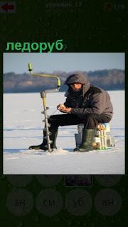 сидит рыбак зимой и рядом стоит ледоруб, которым делает лунку во льду
