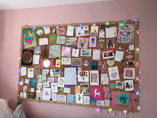 A giant notice board with coloured lights around it. The notice board is filled with cards, postcards and other items.