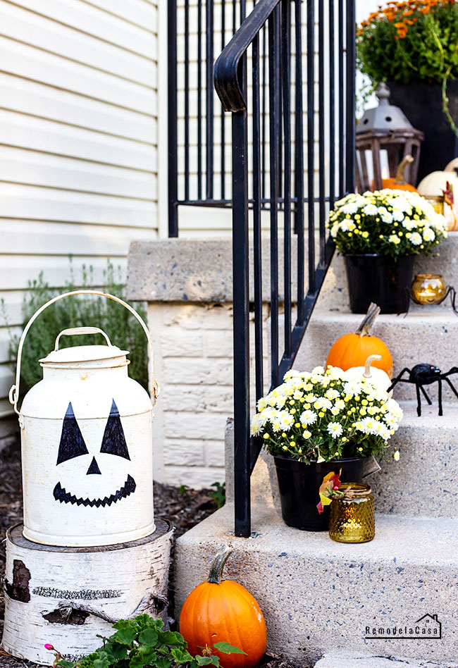 metal lantern with scary face and pumpkins on steps