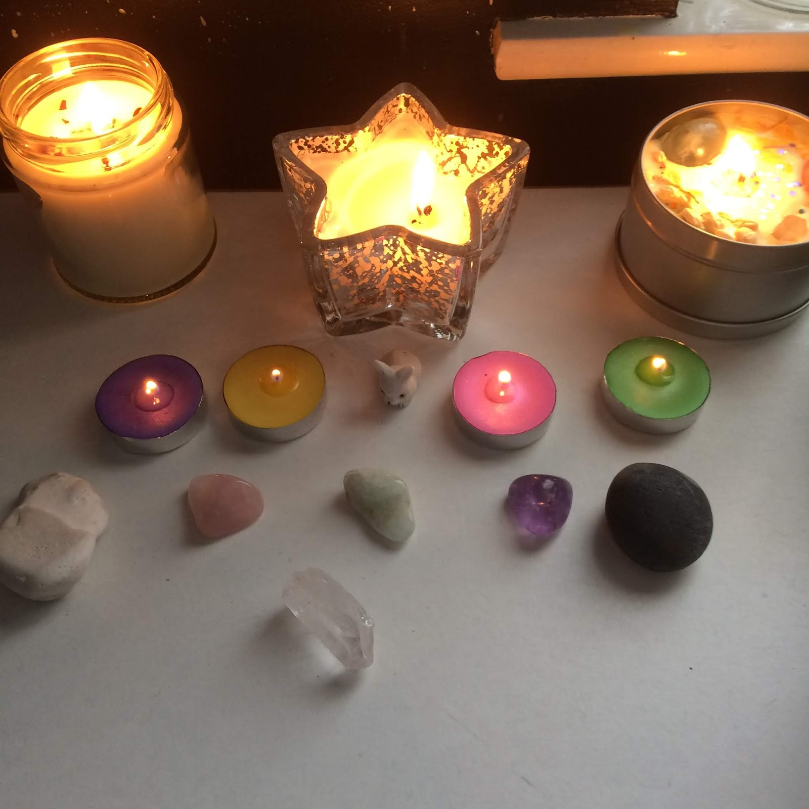 A close up of my Ostara altar, featuring the Ostara candle, a star shaped container candle, and my Feast of Lovers container candle lined up at the back. There are purple, yellow, pink and green tea lights lit in front of the container candles in a row, with a tiny bunny ornament in the centre. Next is a white stone, a rose quartz tumblestone, an aquamarine tumblestone, an amethyst tumblestone, and a black stone. In front, in the centre, is a clear quartz point