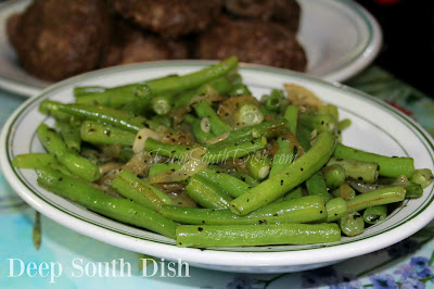 Fresh green beans, quickly skillet blanched, then stir fried with sweet onion, garlic, a hint of brown sugar and herbs.