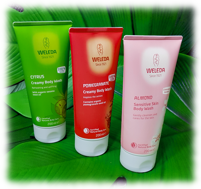 All 3 Weleda body washes pictured on large green leaves