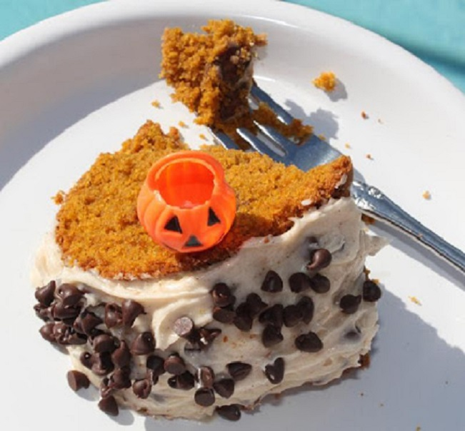 this is a slice of cake with cream cheese frosting sprinkled with mini chocolate chips and a plastic pumpkin pick on top