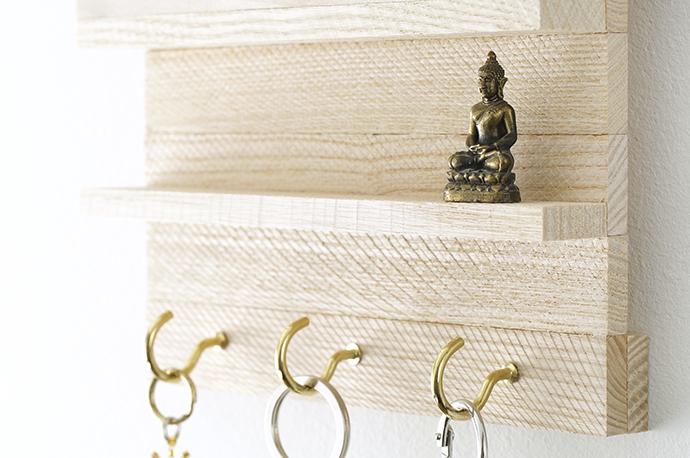 Nahaufnahme Schlüsselboard mit Haken und kleinem Buddha
