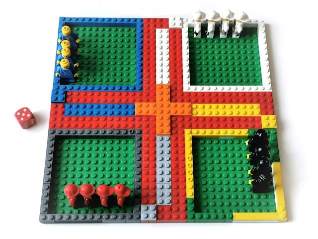 na zdjęciu gra chińczyk zbudowana z klocków lego na zielonej płytce, za pionki posłużyły ludziki lego