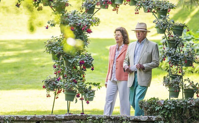 Queen Silvia wore pink blazer and white trousers. Silvia wore a floral print silk blouse