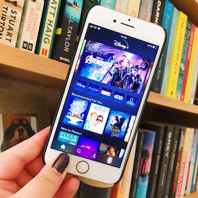 Disney+ app on phone held up in front of bookshelf