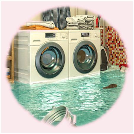 """Taustalla ympäröivän työtilan lainehtimiseen """"syyllinen"""", rikkoutunut pesukone, jota ympäröi sisätiloissa harvoin tavattu, melkoinen tulva."""