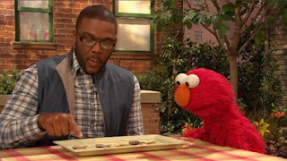 Tyler Perry shows to Elmo his math plate and math skills. Sesame Street Episode 4420, Three Cheers for Us, Season 44