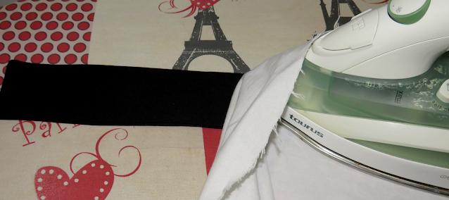 Planchado de la costura de asentamiento usando un trapo para proteger la tela