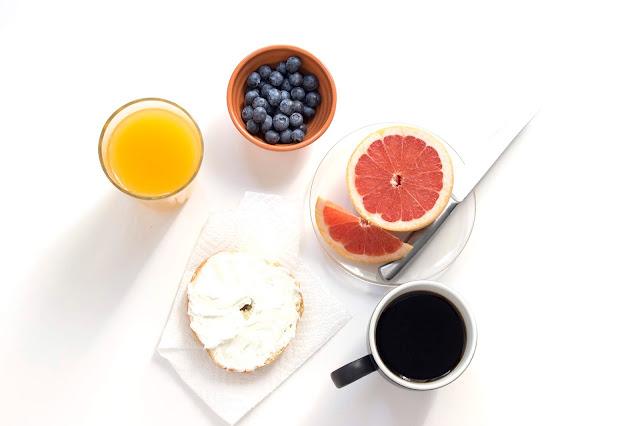 Comida Saudável sobre mesa branca; Laranja, uvas, suco de laranja, pão com queijo