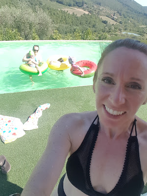 A woman stands in front of a family in bright coloured floaties in a pool