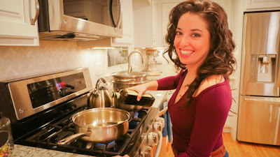Cara in her kitchen at the stove, cooking