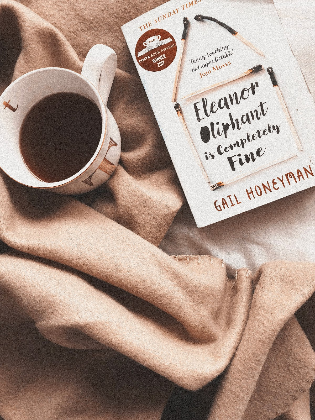 A flatlay containing a brown blanket, a mug of black coffee and a book