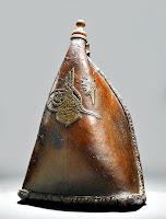 Üzerinde bir Osmanlı Tuğrası bulunan kahverengi deriden yapılmış eski bir su kırbası veya tulumu