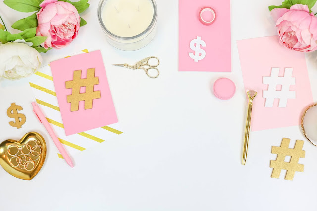 Pink and gold cutouts of hashtags.