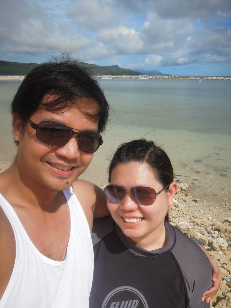 Couple travel bloggers in Misibis Bay's beach