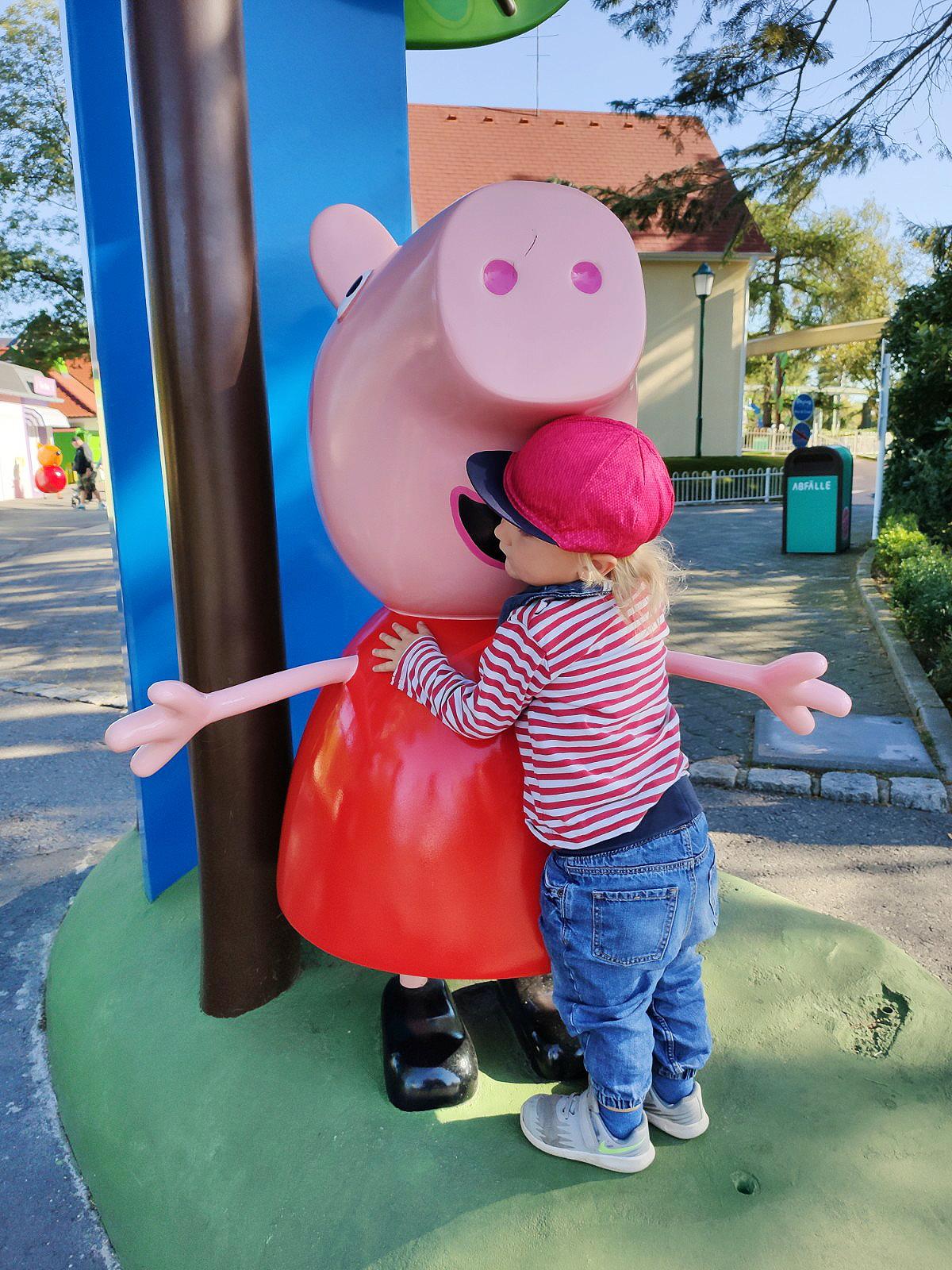 Kleines Kind umarmt große Peppa Wutz Figur
