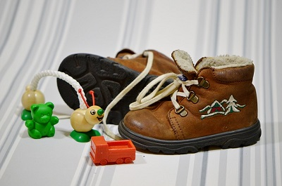 Baby Boy High-Top Brown Shoes with a Few Scattered Toys