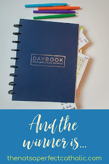 "blue planner with different color markers above it and stickers sticking out of the planner with the text ""And the winner is"" below the planner"