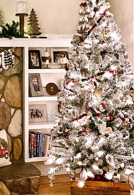 Flocked Christmas tree in front of bookshelf