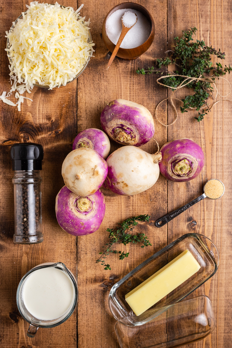 Overhead photo of the ingredient needed to make Turnips Au Gratin on a wooden table.