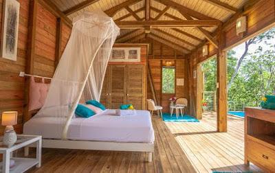 Chambre avec lit double et moustiquaire face à la piscine