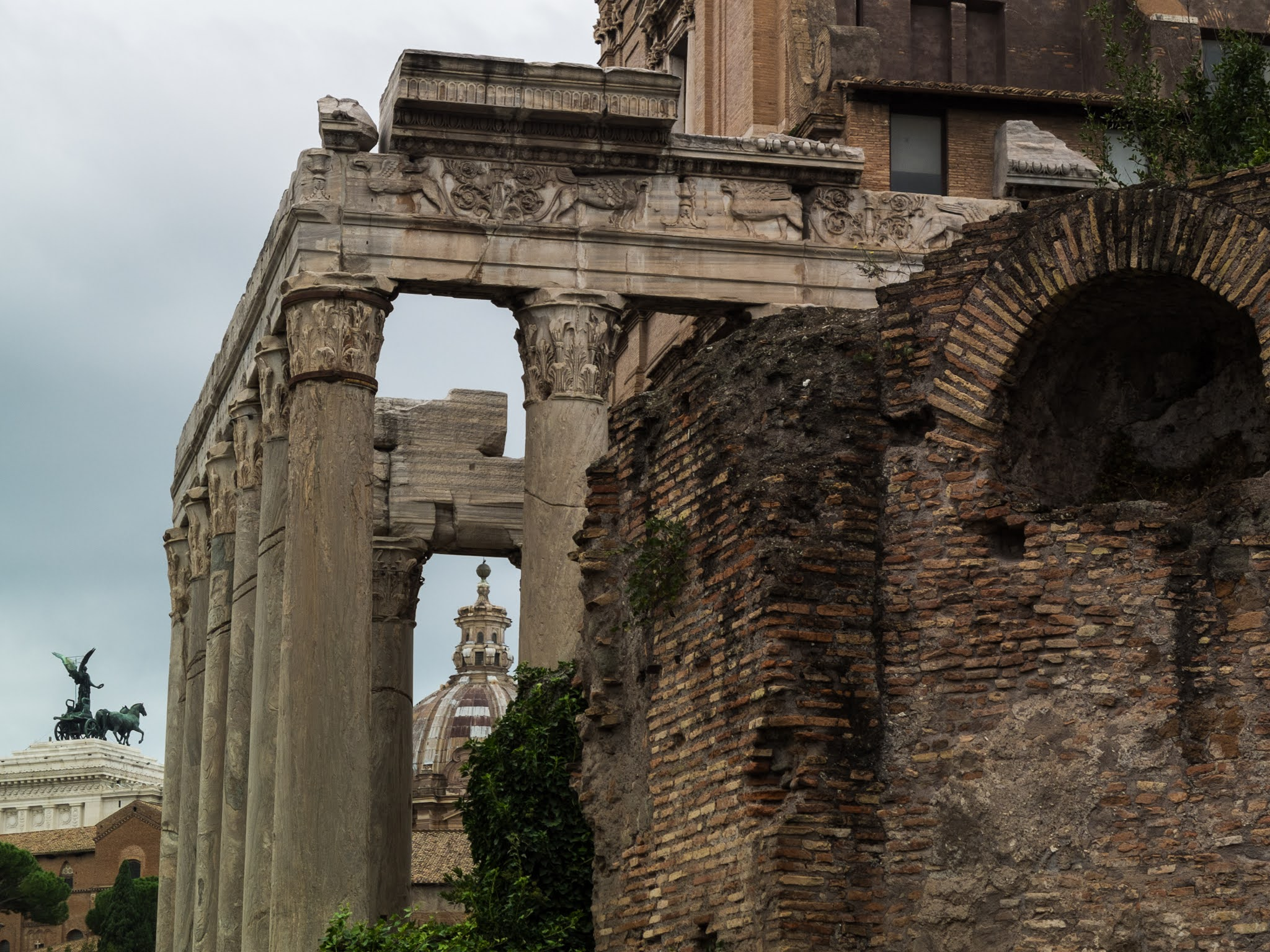 Side view of the Temple of Antoninus and Faustina with red brick ruins to the right.