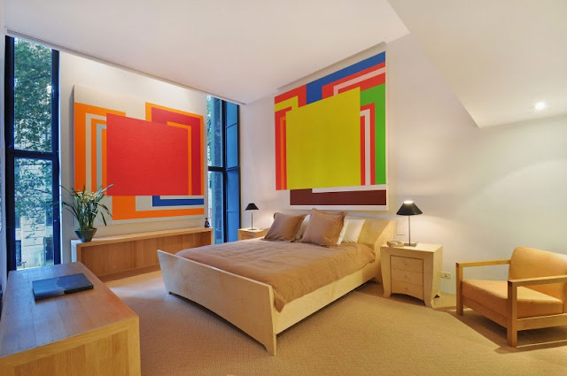 Photo of the same bedroom with wooden furniture and apstract art on the walls