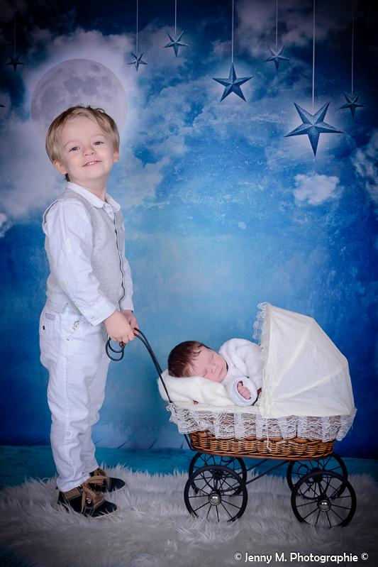 photo studio grand frère avec bébé dans landau en osier