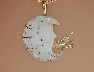Yellow gold pendant w/ carved white drusy moonface and diamond