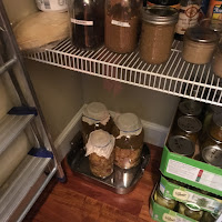 Photo of jars of apple scraps in solution fermenting in a tray in the pantry. https://trimazing.com/