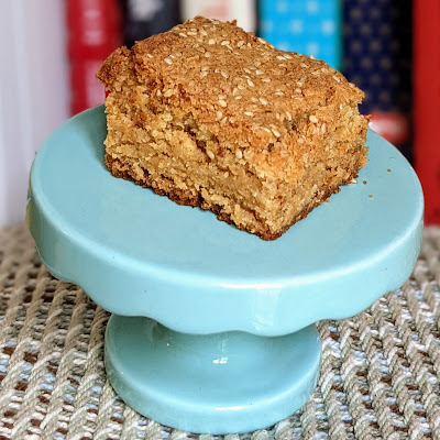 A tan colored blondie with sesame seeds on top sits on a miniature turquoise cake platter.