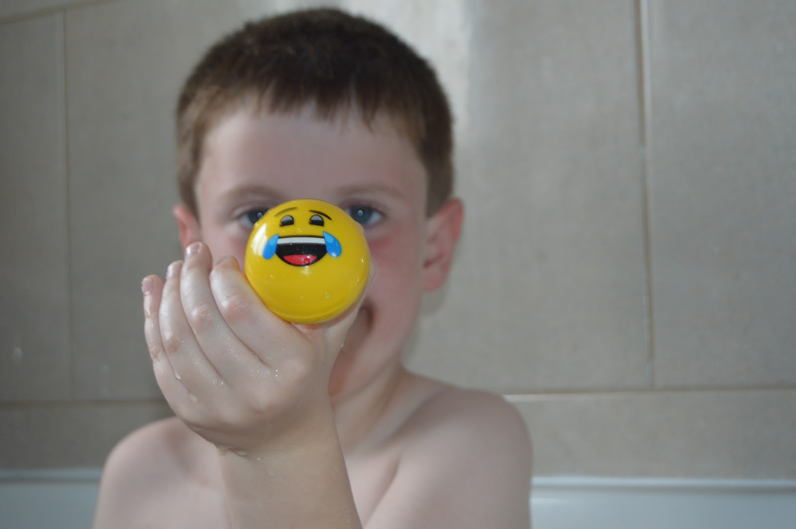 boy holding up a ball in the bath