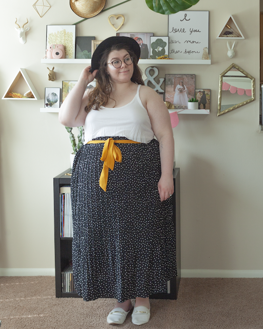 An outfit consisting of a black wide brim fedora, a white layered tank top tucked into a white on black dotted pleated midi skirt and white mules.