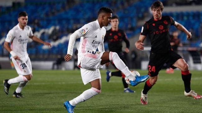 Real Madrid harus puas bermain imbang 1-1 melawan Real Sociedad dalam lanjutan LaLiga. Gol Vinicius Junior di penghujung laga yang menyelamatkan Los Blancos dari kekalahan. Bertanding di Stadion Alfredo Di Stefano, Selasa (2/3/2021) dini hari WIB, Madrid sanggup menggempur pertahanan Sociedad. Namun, hingga turun minum skor 0-0 tak berubah.  Sociedad mampu unggul duluan di babak kedua lewat Portu. Madrid selamat dari kekalahan setelah Vinicius Junior melesakkan gol di penghujung laga.  Madrid kini ada di posisi ketiga dengan 53 poin, sama kalah selisih gol dengan Barcelona di tempat kedua. Jarak El Real dengan Atletico Madrid juga menjadi lima poin. Sociedad ada di urutan kelima dengan 42 angka.  Real Madrid vs Real Sociedad – Highlights  <iframe width='100%' height='400' src='https://yfl.ahdafsoccer.com/embed/67jBYYZVhgwa7' style='border:none;' allowfullscreen></iframe>  Susunan Pemain:  Real Madrid: Thibaut Courtois; Lucas Vasquez, Nacho, Raphael Varane, Ferland Mendy; Casemiro, Toni Kroos, Luka Modric; Marco Asensio, Isco, Mariano.  Sociedad: Alex Remiro; Andoni Gorosabel, Igor Zubeldia, Robin Le Normand, Nacho Monreal; Ander Guevara, Martin Zubimendi; Portu, David Silva, Mikel Oyarzabal; Alexander Isak.