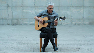 Old man sitting on a chair in a white space, playing acoustic guitar