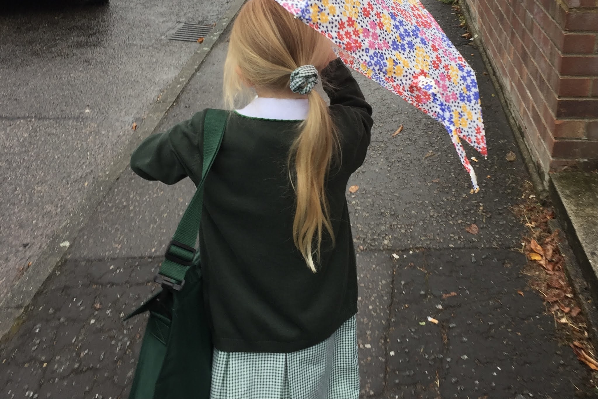 A school child going home from school in the rain in a bad mood