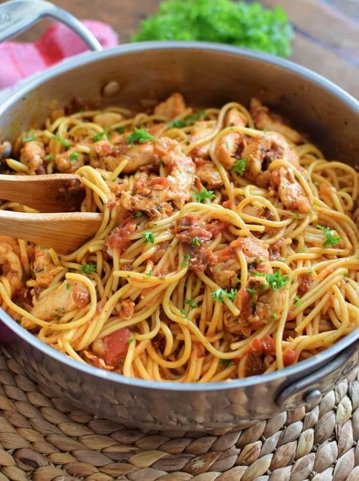 Espaguetis con pollo en salsa de tomate presentado en una sartén grande donde se hizo la cocción