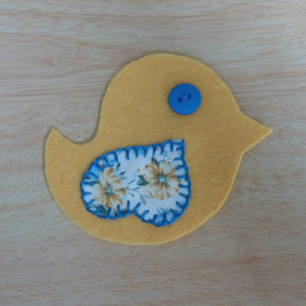 Yellow bird pattern piece with fabric wing sewn on and blue button eye