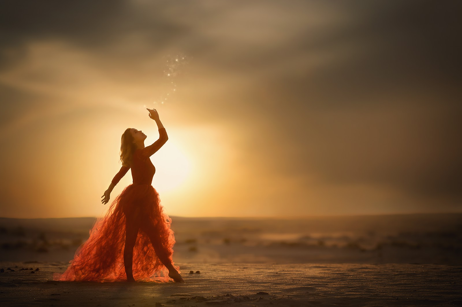 Dreamy canon image of a woman dressed up like a fairy in a red dress playing with magic fire flies in the desert during sunset by Willie Kers.