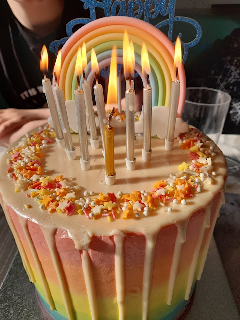 The top of the rainbow cake. White melted chocolate with rainbow sprinkles has 10 lit candles on
