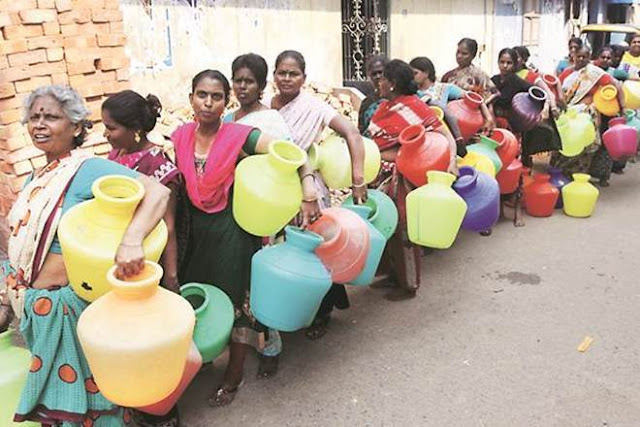 Indian women stand in line and waiting to fill water