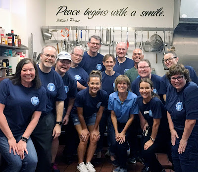 "group photo of staff in kitchen.  Sign above reads, ""Peace begins with a smile."""